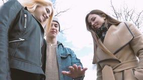 I giovani camminano nel parco, dicono le notizie, comunicano, ridono Buon umore Un le vostre mani archivi video