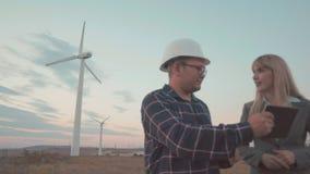 I giovani in caschi sui precedenti dei mulini a vento considerano il progetto in una compressa digitale Affare di costruzione stock footage