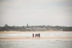 I giovani che stanno nel mare in Punta fanno Ouro nel Mozambico Fotografie Stock Libere da Diritti