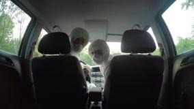 I giovani colleghi dei tecnici degli scienziati di rischio biologico nei vestiti del hazmat in automobile girano l'esame del sedi video d archivio