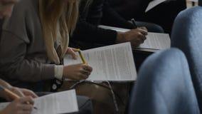 I giovani compilano i questionari, ponenti fogli sulle loro ginocchia video d archivio