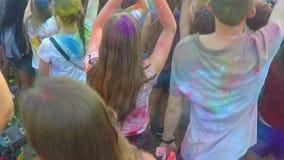 I giovani coperti in Holi colorano godere della musica e divertiresi al festival stock footage