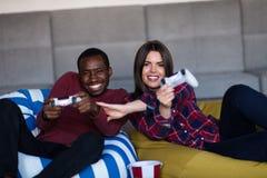 I giovani coppia a casa il gioco del video gioco insieme immagine stock libera da diritti