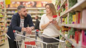 I giovani coppia l'acquisto in una drogheria Famiglia felice che ha molto divertimento che spende insieme tempo Ricerca dell'alcu stock footage