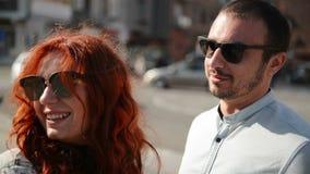 I giovani coppia tenersi per mano mentre camminano gi? una via della citt? che parlano e che sorridono insieme stock footage