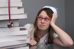I giovani curano con il cappuccio che esamina la pila di libri Fotografie Stock Libere da Diritti