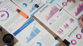 I giovani direttori aziendali di vista superiore analizzano i documenti, piani per il nuovo progetto startup in ufficio stock footage