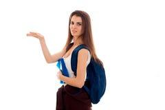 I giovani dispiacere la ragazza castana dello studente con lo zaino sulle suoi spalle e libri in sue mani che indica il lato e Fotografia Stock
