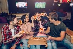 I giovani divertenti si siedono insieme nella sala e mangiano la pizza Giocano con i suoi pezzi Risata dei compagni di squadra immagini stock libere da diritti