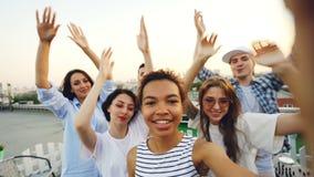 I giovani e gli amici allegri delle donne stanno ballando sollevando le mani e divertendosi al partito del tetto di estate Stile  stock footage