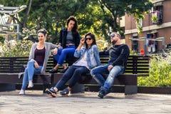 I giovani ed attraenti stanno sedendo su un banco in via del ghetto Fotografia Stock