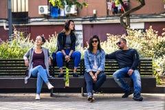 I giovani ed attraenti stanno sedendo su un banco in via del ghetto Fotografie Stock Libere da Diritti