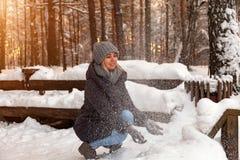 I giovani edifici occupati biondi in una foresta dell'inverno in un cappello grigio ed in un rivestimento blu scuro e guarda la c fotografia stock