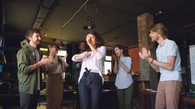 I giovani felici stanno ballando nel cerchio alla festa dell'ufficio, mani d'applauso e stanno ridendo godendo della festa corpor video d archivio