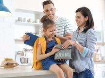 I giovani genitori che aiutano il loro piccolo bambino si preparano per la scuola immagini stock