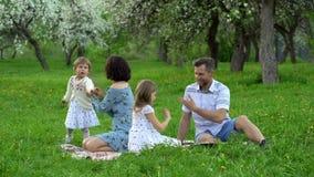 I giovani genitori con due figlie spendono lo svago su un plaid in parco sulla molla archivi video