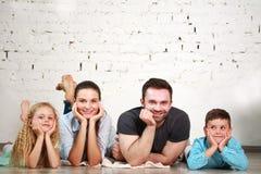 I giovani genitori felici della famiglia e due bambini si dirigono lo studio immagini stock libere da diritti