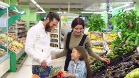I giovani genitori felici fanno gli acquisti con la loro figlia nel supermercato archivi video