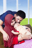 I giovani genitori musulmani baciano il loro bambino Fotografie Stock Libere da Diritti