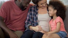 I giovani genitori trovano l'approccio per lanciare la famiglia amorosa e preoccuparsi adottata del bambino, fotografia stock