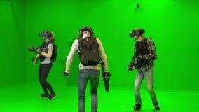 I giovani giocano in gruppo nella realtà virtuale su un fondo verde Gioco del tiratore di VR con prova della cuffia avricolare di archivi video