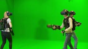 I giovani giocano in gruppo nella realtà virtuale in un casco di VR su un fondo verde stock footage