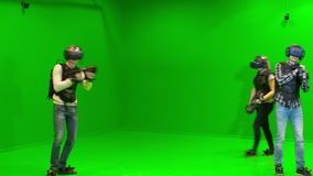I giovani giocano in gruppo nella realtà virtuale in un casco di VR su un fondo verde archivi video