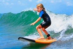 I giovani giri del surfista sul surf con divertimento sul mare ondeggia immagini stock