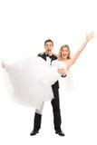 I giovani governano il sollevamento della sua sposa in sue mani Immagine Stock