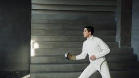 I giovani hanno concentrato la pratica dell'uomo dello schermitore che recinta gli esercizi e che si prepara per la concorrenza d Immagini Stock