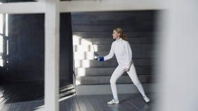 I giovani hanno concentrato la pratica della donna dello schermitore che recinta gli esercizi e che si prepara per la concorrenza Fotografia Stock
