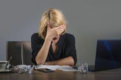 I giovani hanno frustrato e sollecitato gridare della donna di affari triste alla scrivania che funziona con il computer portatil immagini stock libere da diritti