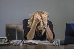 I giovani hanno frustrato e sollecitato gridare della donna di affari triste alla scrivania che funziona con il computer portatil fotografia stock