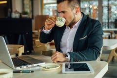 I giovani hanno messo a fuoco l'uomo d'affari che si siede nel café, lavorante al suo lapto Fotografie Stock