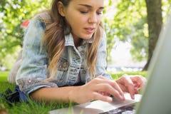 I giovani hanno messo a fuoco lo studente che si trova sull'erba facendo uso del suo computer portatile Immagini Stock Libere da Diritti