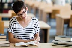 I giovani hanno sollecitato la ragazza dello studente che studia il mucchio dei libri Fotografia Stock