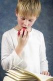 I giovani hanno stupito il ragazzo che legge un libro con la mela sana rossa nel suo ha Fotografie Stock