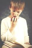 I giovani hanno stupito il ragazzo che legge un libro con la mela sana rossa nel suo ha Immagini Stock Libere da Diritti