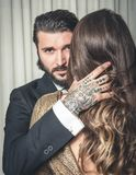 I giovani hanno tatuato il ritratto dell'uomo vestito elegante abbracciando un biondo Fotografie Stock