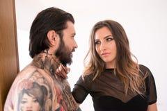 I giovani hanno tatuato l'uomo che interagisce con una donna sexy nella entrata Fotografie Stock