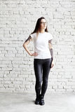 I giovani hanno tatuato la donna che porta la maglietta in bianco, stante davanti al muro di mattoni in sottotetto Fotografie Stock Libere da Diritti