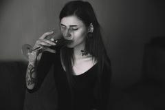 I giovani hanno tatuato la donna con il vino bevente dei capelli lunghi Immagine Stock Libera da Diritti