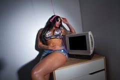 I giovani hanno tatuato molto la donna che si siede su una tavola che guarda una TV Fotografie Stock