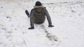I giovani hanno vestito alla moda l'uomo mentre camminare nel parco nell'inverno ha slittato e perso il suo equilibrio fotografie stock libere da diritti