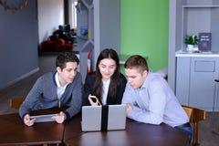 I giovani impiegati della società sono donne ed uomini che fanno le tavole e la c Fotografia Stock Libera da Diritti