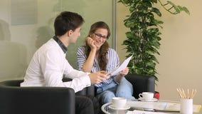 I giovani impiegati discutono a fondo la tazza di caffè nella grande società video d archivio