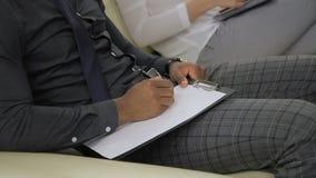I giovani impiegati sono scrivere, sedentesi alla conferenza di funzionamento nell'ufficio moderno all'interno archivi video