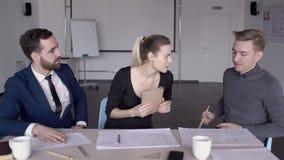 I giovani impiegati stanno lavorando alla tavola in ufficio moderno all'interno stock footage