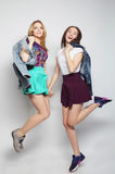 i giovani migliori amici delle ragazze dei pantaloni a vita bassa saltano Immagini Stock Libere da Diritti
