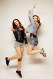 i giovani migliori amici delle ragazze dei pantaloni a vita bassa saltano Fotografia Stock